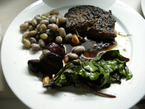 Ribeye steak with deglazing sauce, sauteed beet greens, roasted beets and bortolotti beans.